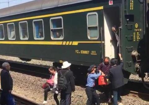 火车未停站台,乘客需跨越铁轨